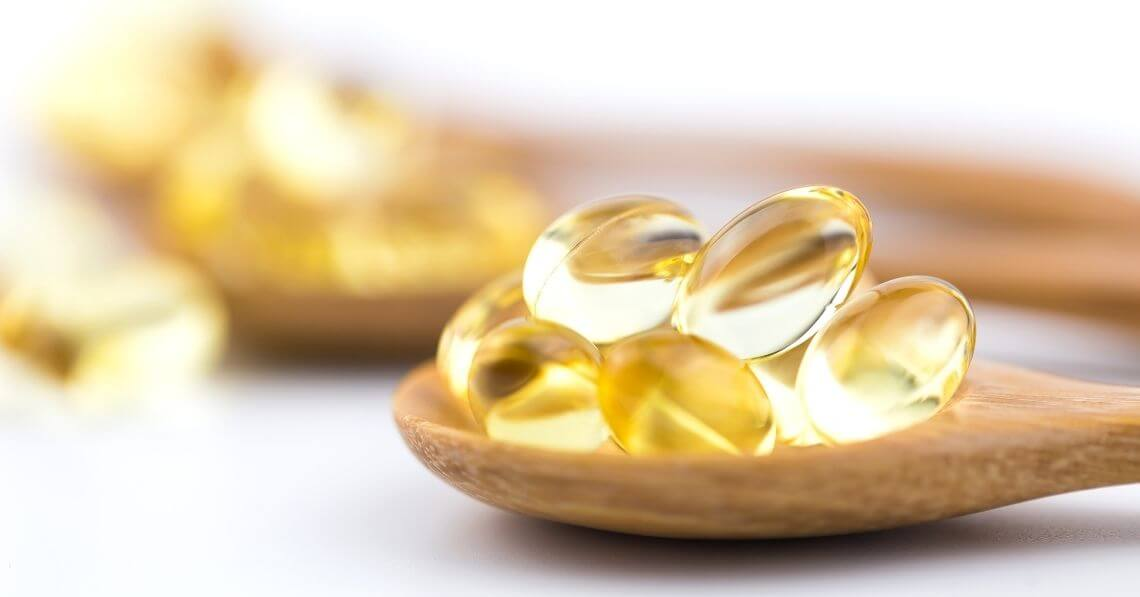 Supplement gel capsules in a wooden spoon