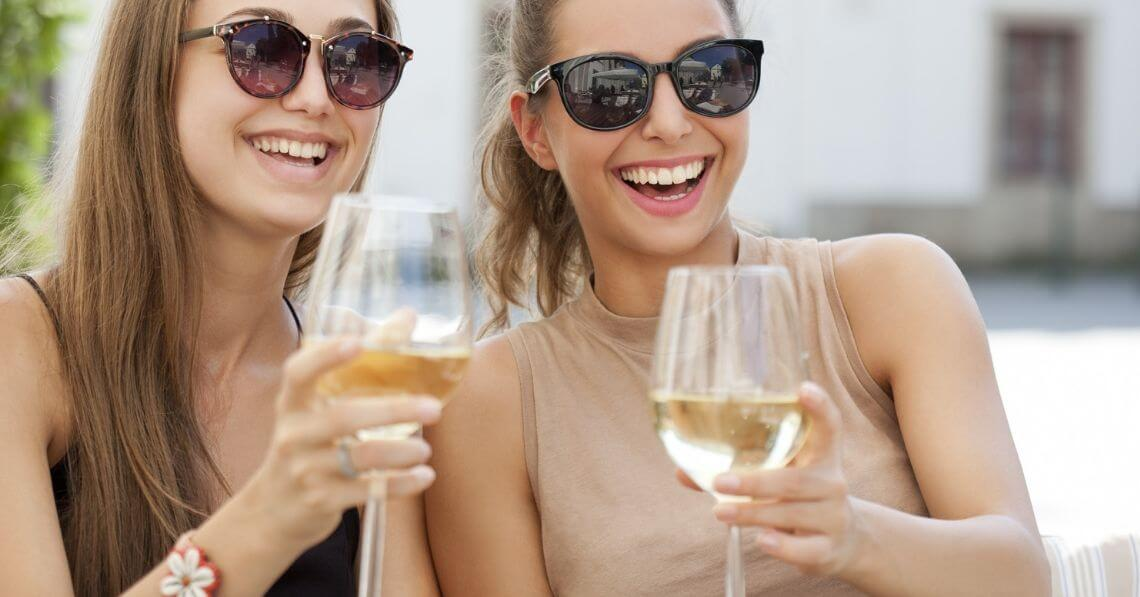 Two young women laughing and enjoying white wine