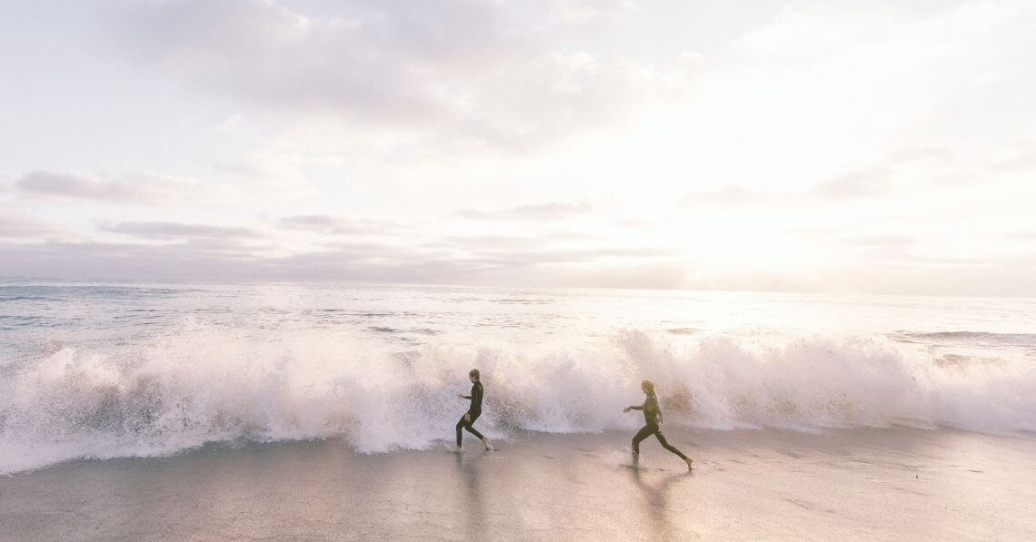 A couple in wetsuit running into the waves
