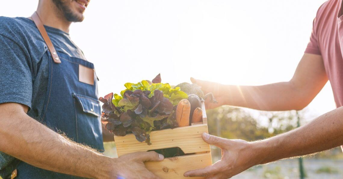 A man handing a woman a box of produce