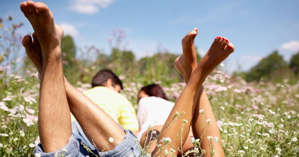 A couple laying in a field among flowers