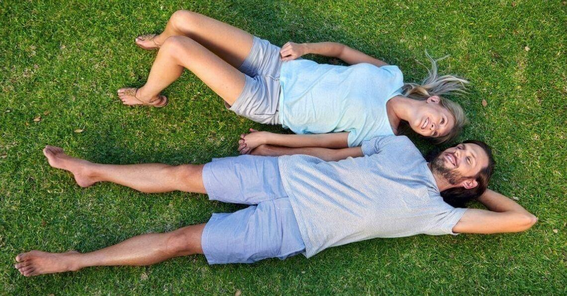 A couple laying on grass