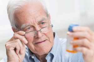 A senior man wearing reading glasses, looking at the label on a bottle of prescription medicine, trying to figure out the instructions