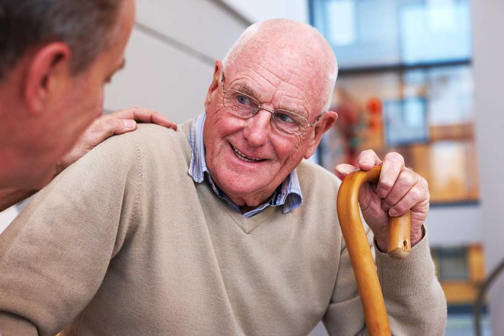Senior man with a walking can sits while enjoying a conversation