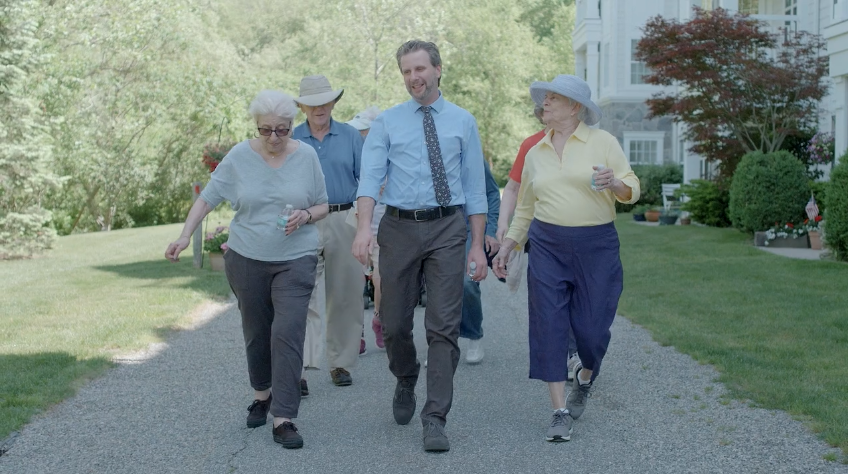 senior living community employee walking with a group of residents