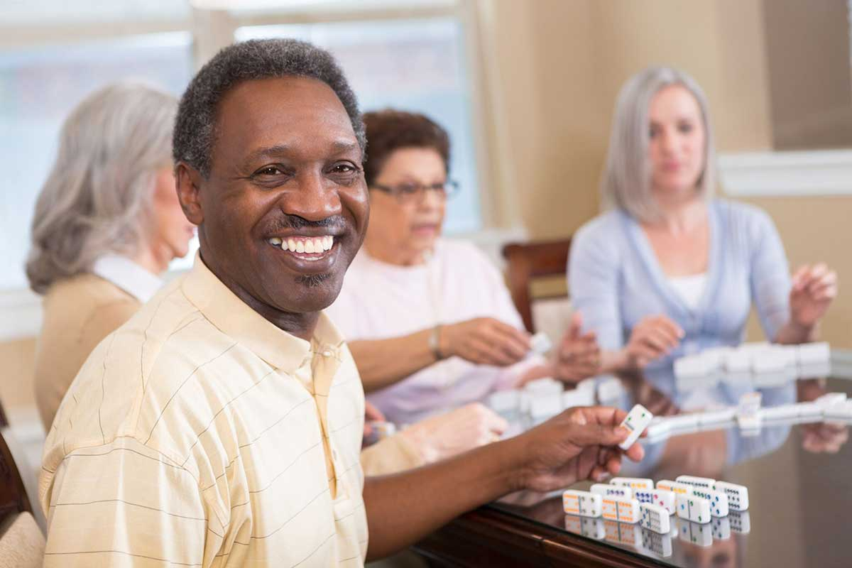 a senior man smiling while playing dominoes with other residents at his senior living community