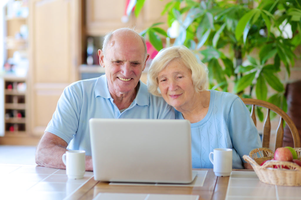 Two smiling people, active senior couple, enjoying modern technology using laptop computer with wireless internet at home