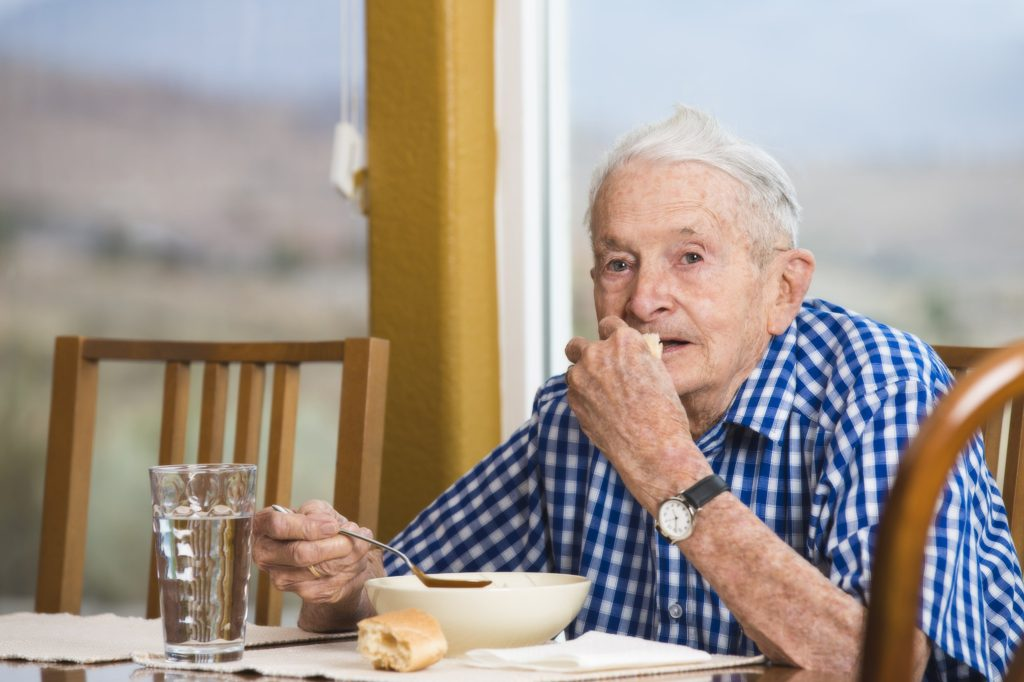elderly man eating food