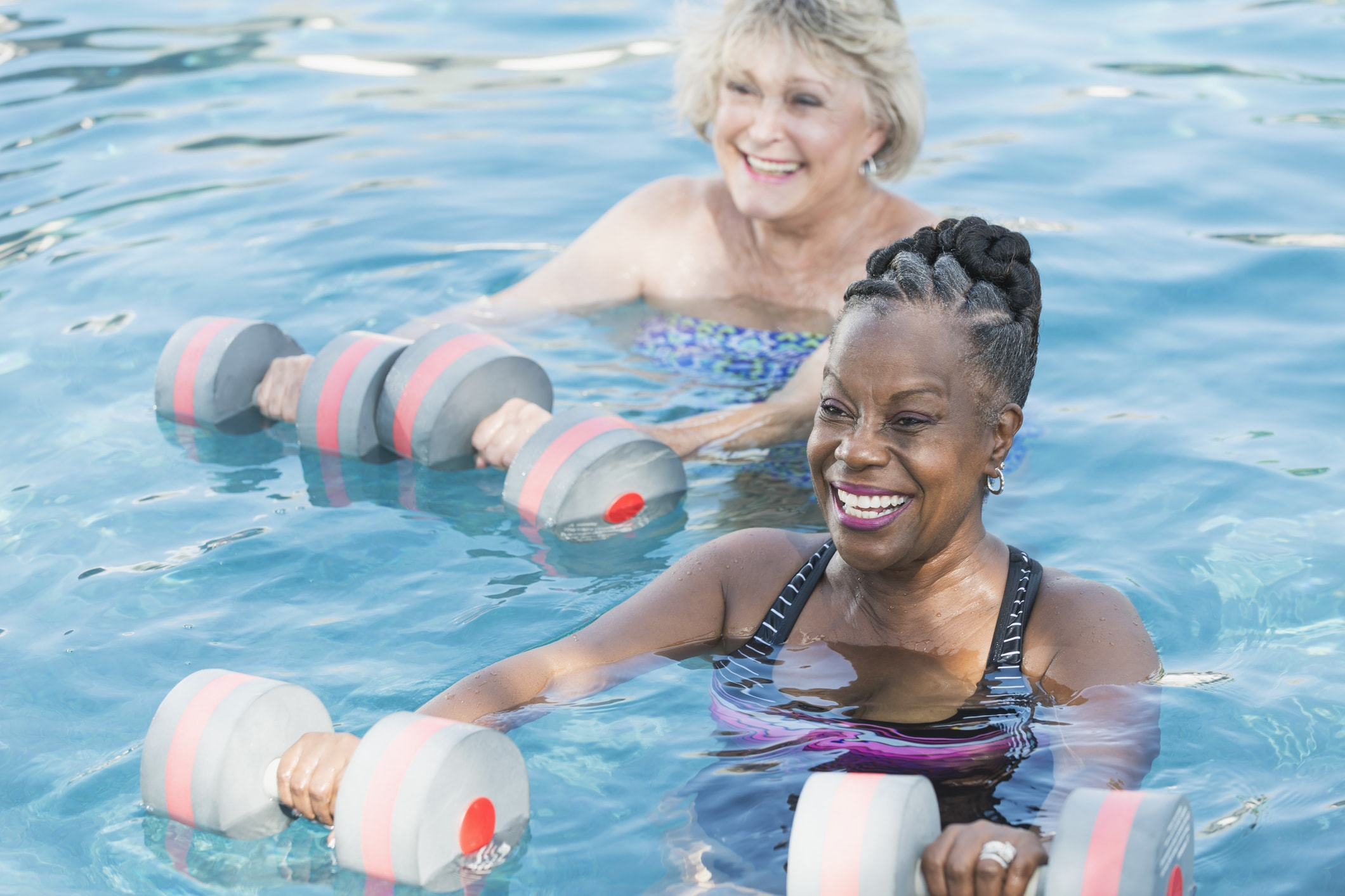 Two elderly women working out in a pool at their senior living community