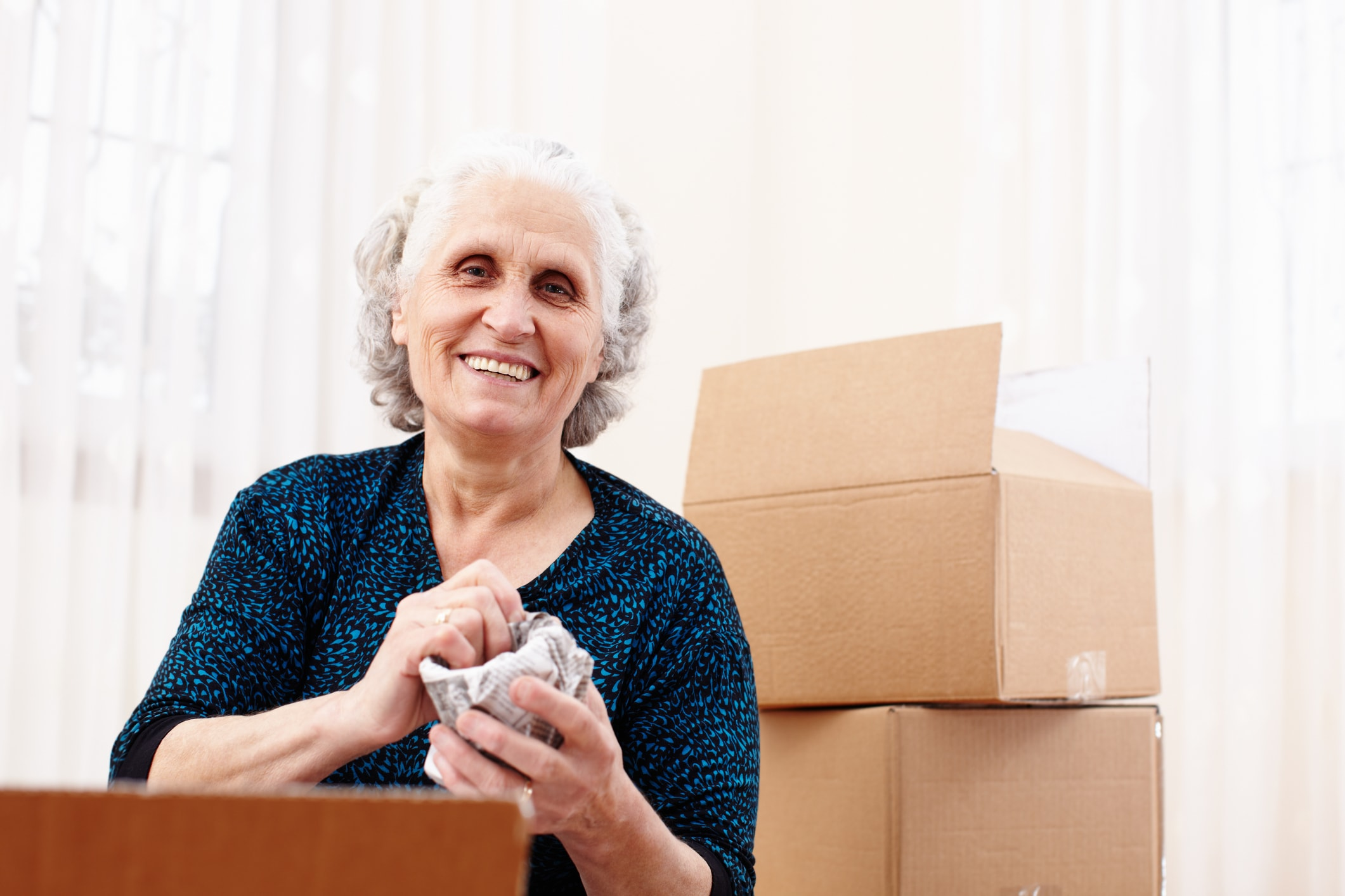 Older woman surrounded by packing boxes for her move to a senior living community