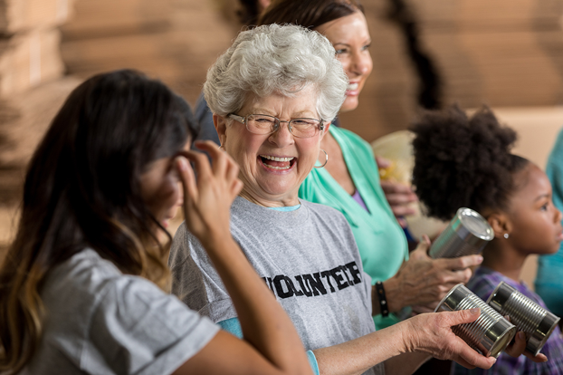 A senior woman smiling while volunteering at a food pantry