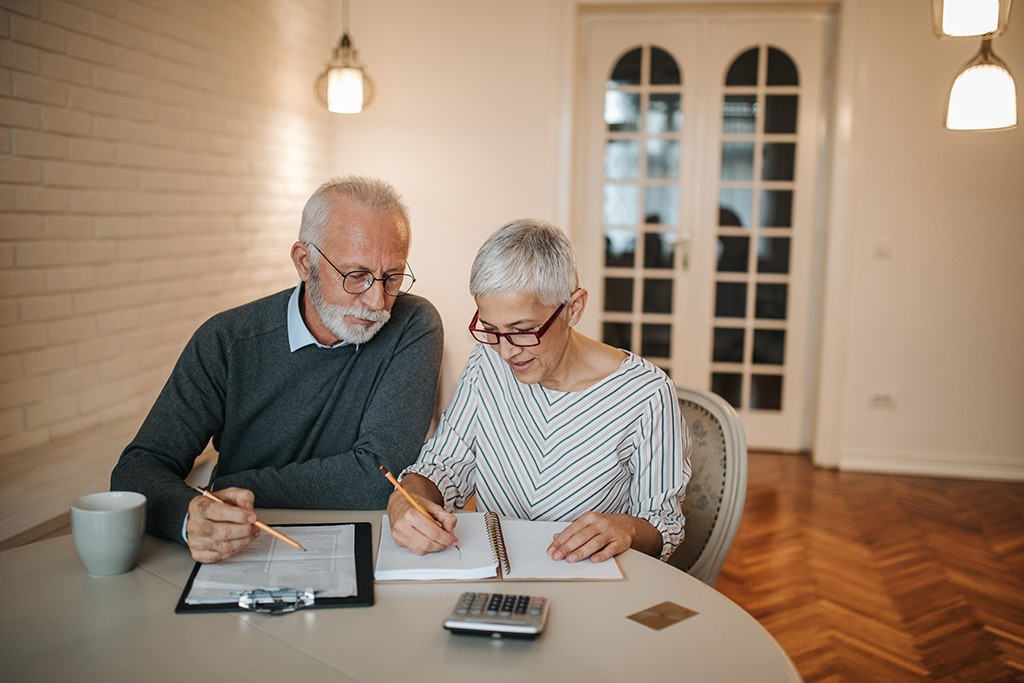 a senior couple working on filing their taxes