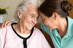 a senior woman smiling with her adult daughter