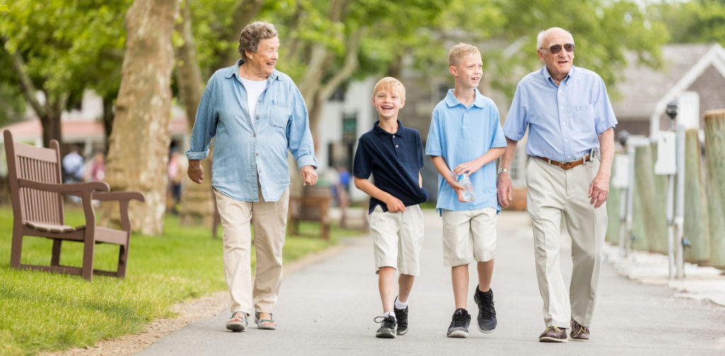 A senior couple taking a walk outside with their two grandsons