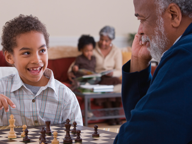 Grandfather and grandson laughing and playing chess