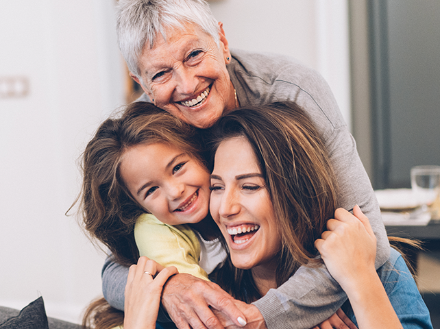 Senior woman hugging her daughter and granddaugther and smiling