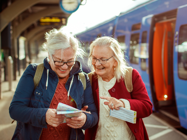 two senior women looking at maps while traveling together