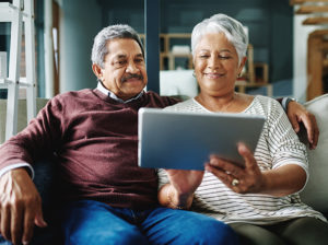a senior couple using a tablet to research rental senior living communities