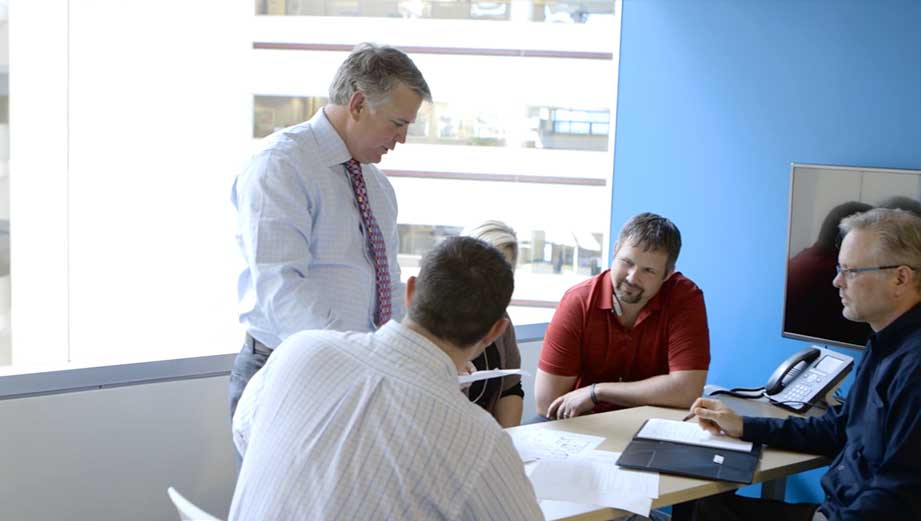 Video still of four men working together in a conference room