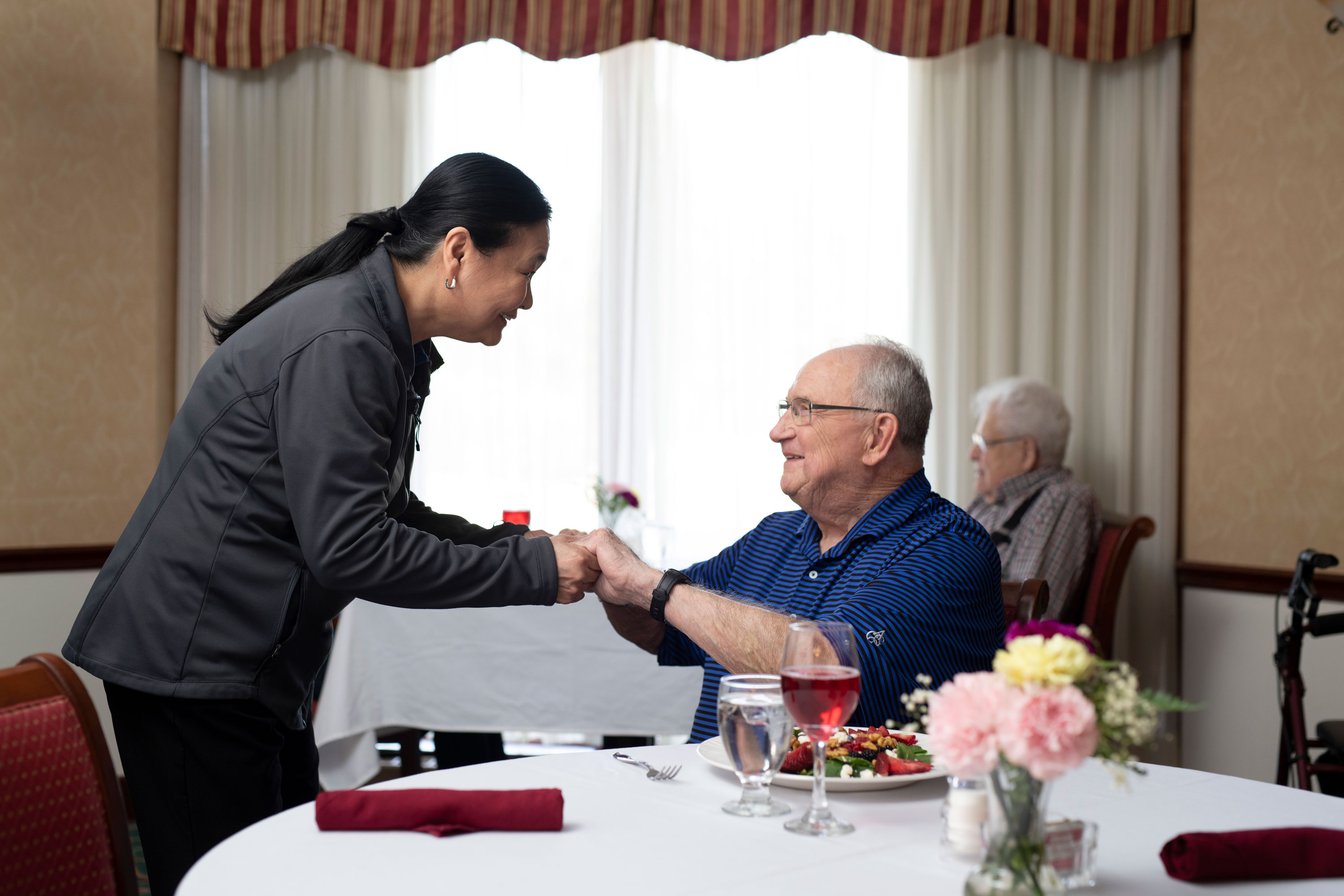 An elderly gentleman thanking the chef for his meal at his senior living community