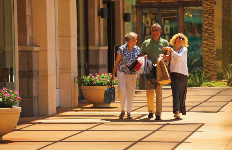 an elderly man and two women holding shopping bags and walking down the street