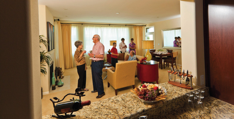 group of seniors spending time together in the living room of a resident's apartment
