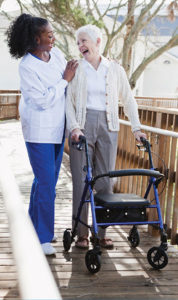 Elderly woman walking outside with her caregiver at a senior living community