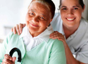 Elderly woman posing and smiling with her caregiver