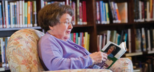 elderly woman reading a book inside her library at her senior living community
