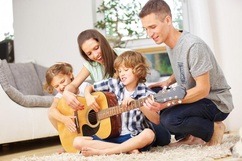 Die Eltern musizieren gemeinsam mit den Kindern im Wohnzimmer