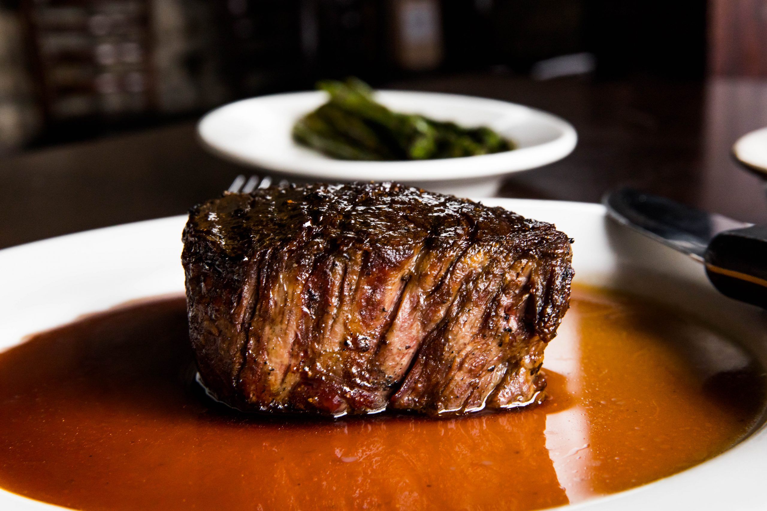 A large filet mignon sitting in au jus