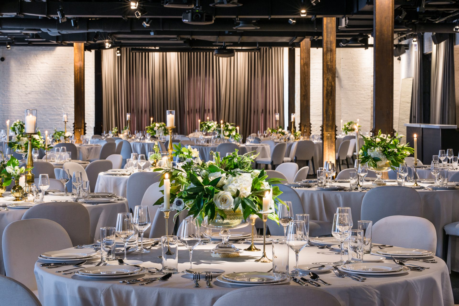 Dalcy event hall. Multiple tables set with plates, glasses, and a bouquet of flowers in the middle.