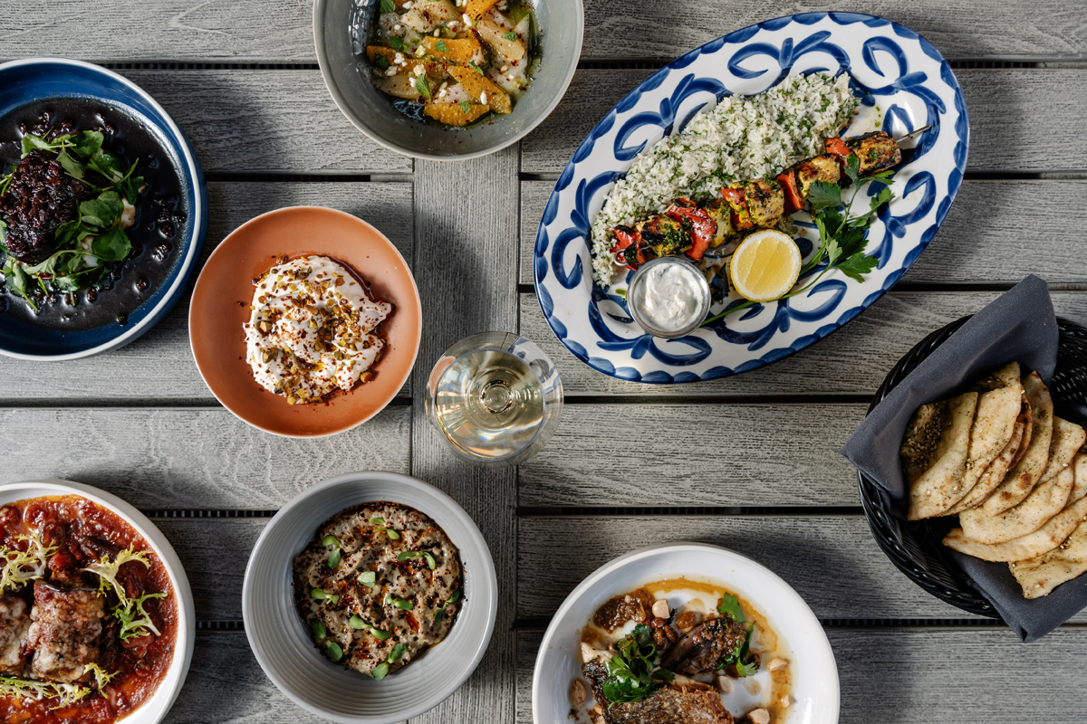 Overhead photo of a variety of dishes including chicken kabobs, pita, and homemade burrata