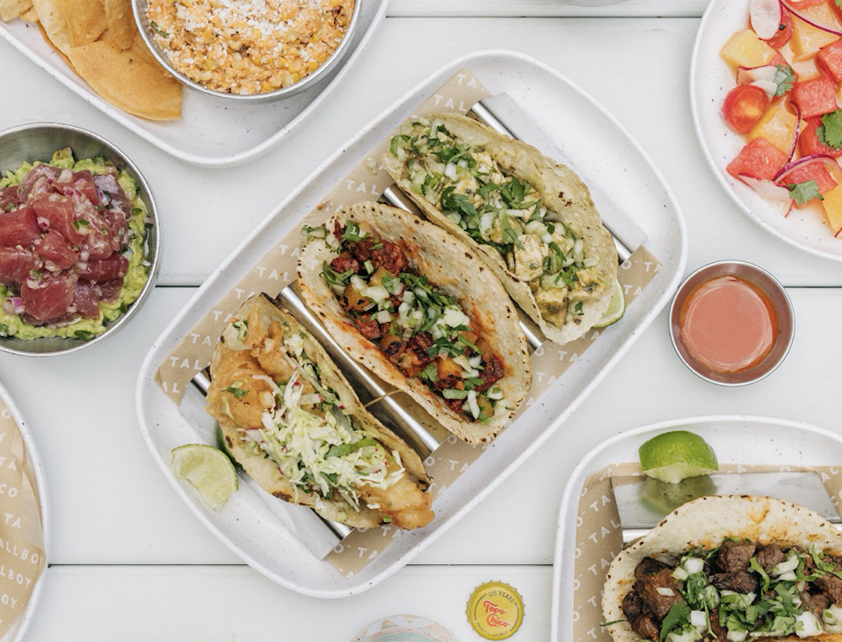 overhead shot of a 3 tacos next to different salads and side dishes