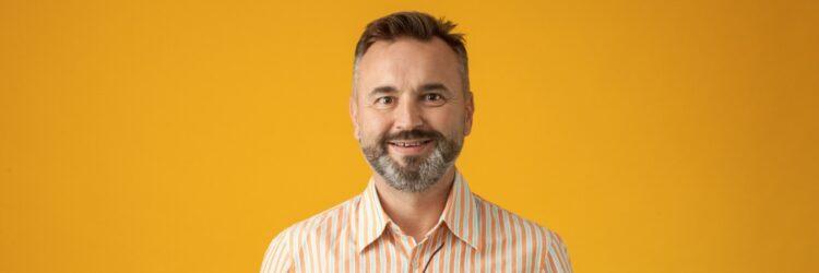 Homme souriant sur fond jaune