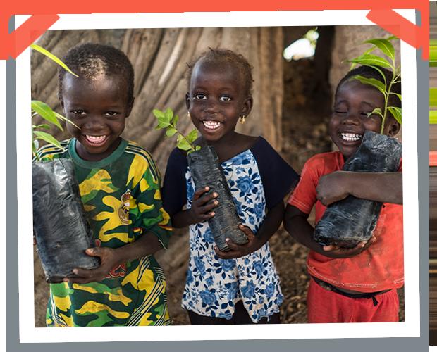 Tres niños felices sosteniendo plántulas en sus brazos