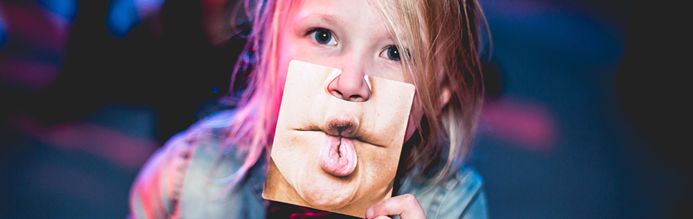 young child holding silly face mask
