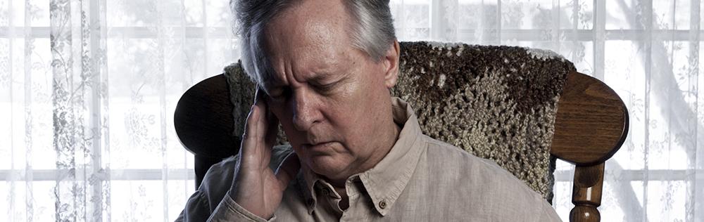 elderly man holding side of head in pain