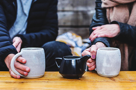 Couple drink a warm beverage together to keep warm during the winter.