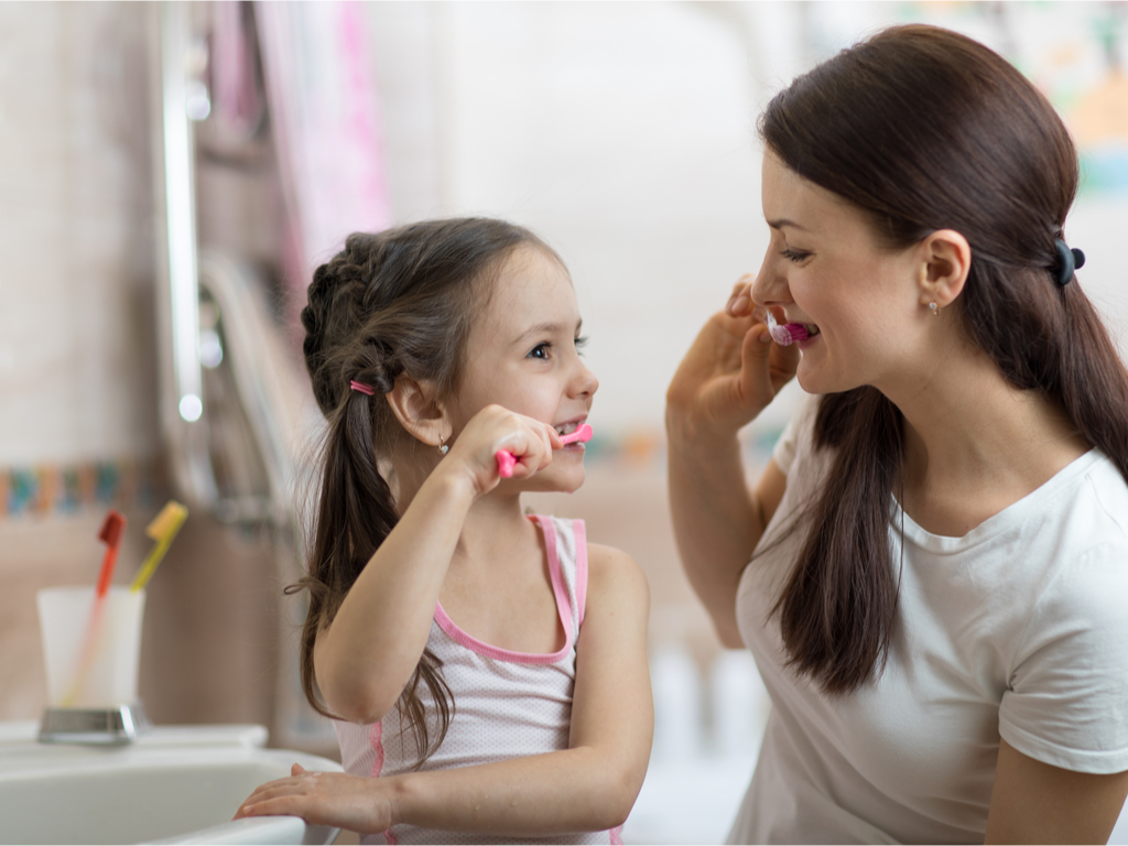 girl brushing with mom