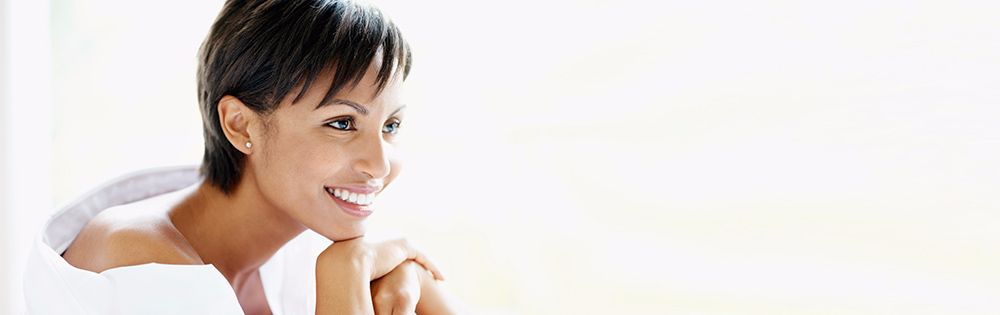 Women with anti-wrinkle injections smiles and relaxes on lounge.