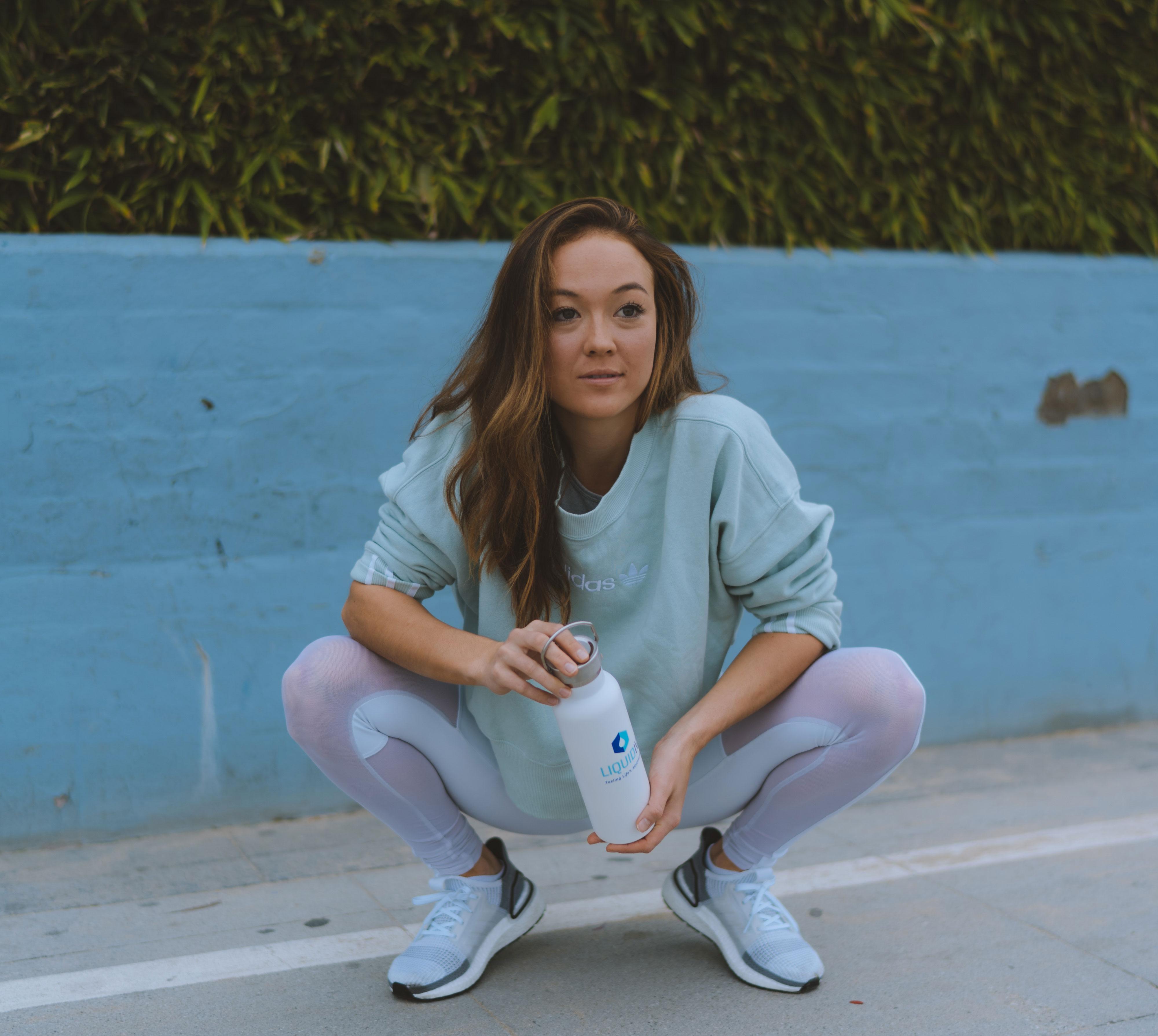 Model on set in squat position holding Liquid I.V. water bottle
