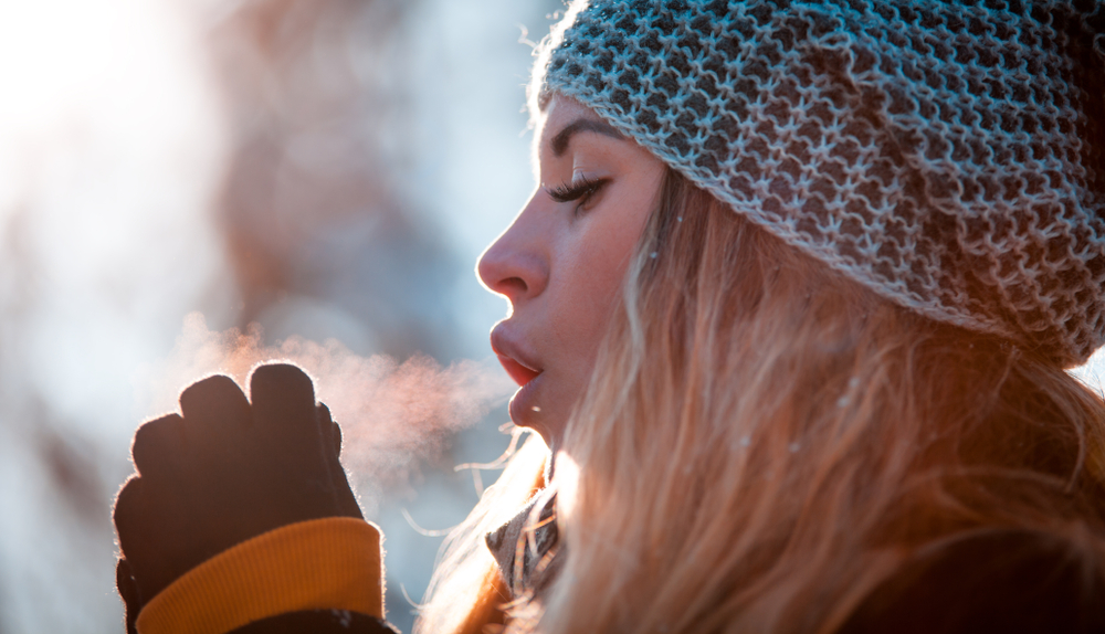 Model exhaling in winter with visible breath