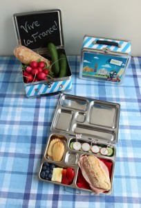 France Bento Box with Little Passports Lunchbox on Blue/White Table Cloth