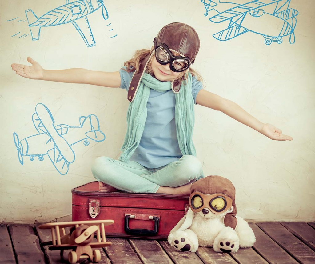 Girl sitting on suitcase wearing flight goggles