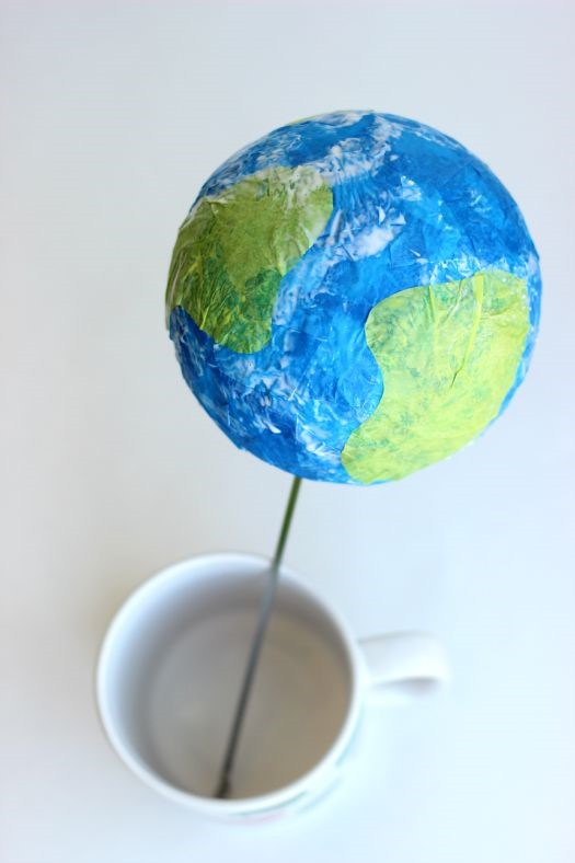 Little Passports Blog DIY Tissue Paper Globe Drying in a mug on a skewer