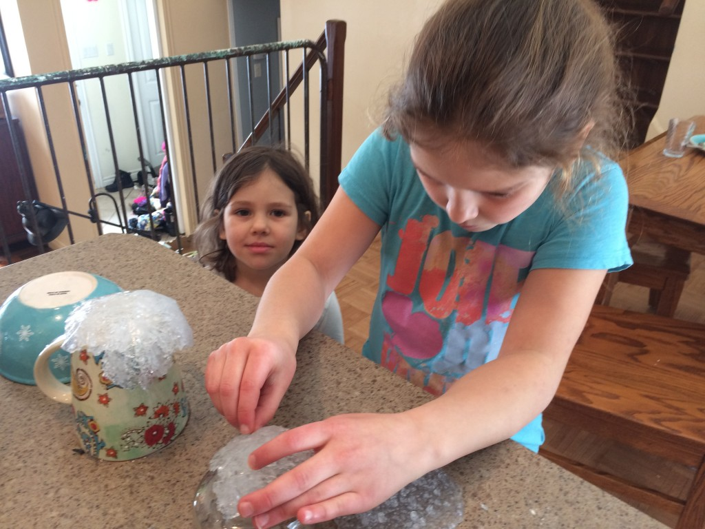 Two girls forming edible geodes over bowls