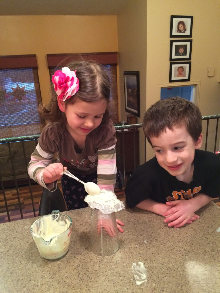 Girl and boy placing melted white chocolate chips over geodes