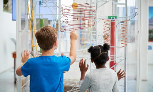 Two,Kids,Looking,At,A,Science,Exhibit,,Back,View