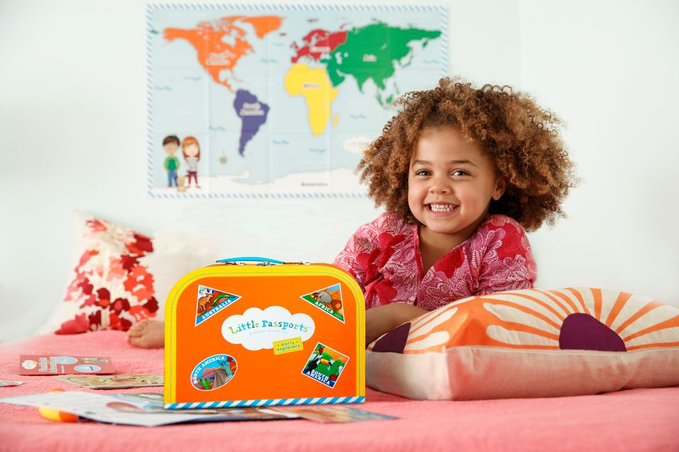 Girl on bed with Early Explorers Suitcase